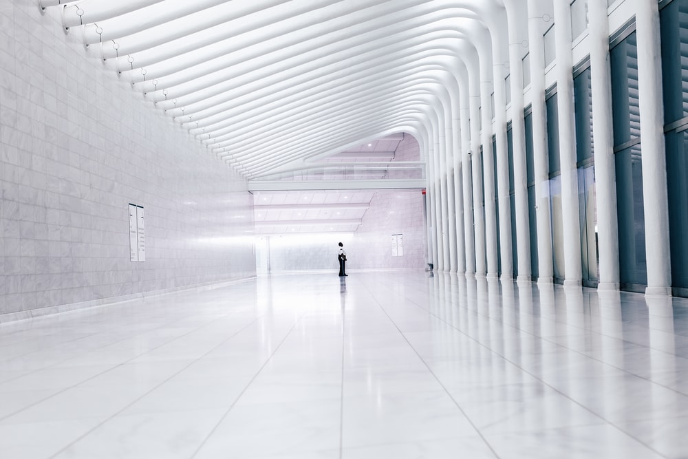 person at end of lobby facing columns