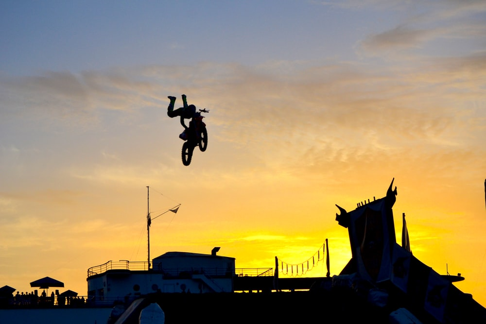 silhouette of person riding motocross dirt bike