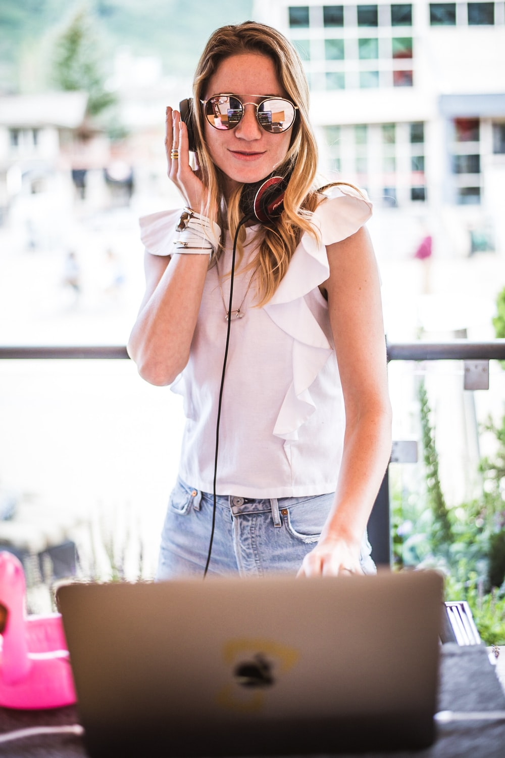 woman standing in front of silver laptop with headphones