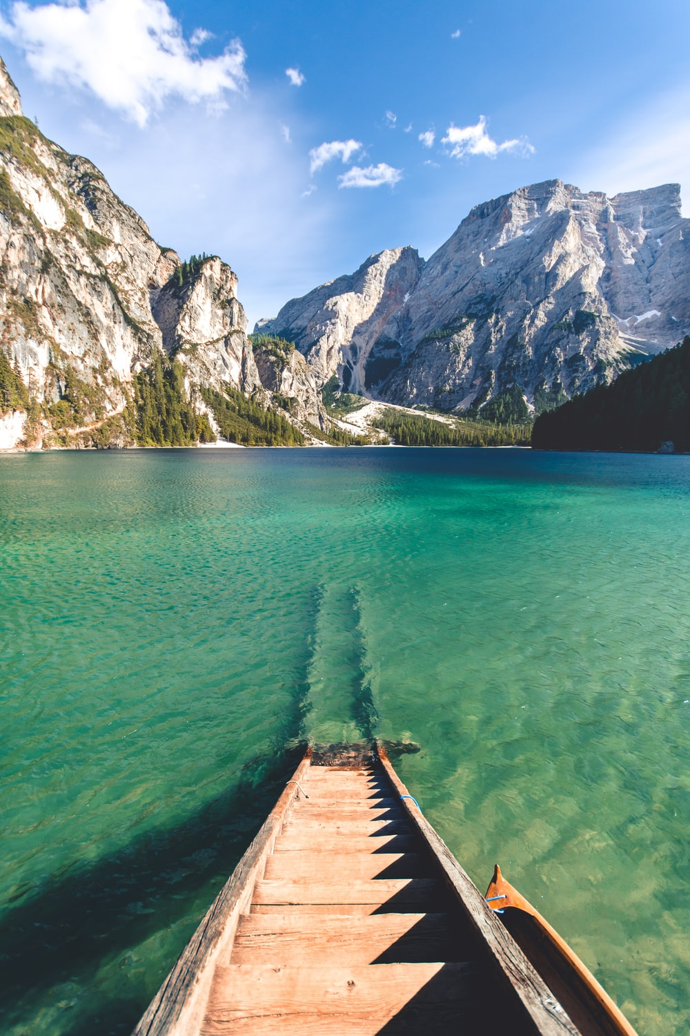 brown wooden wooden ladder submersed in body of water with rocky mountain ahead under white and blue sky