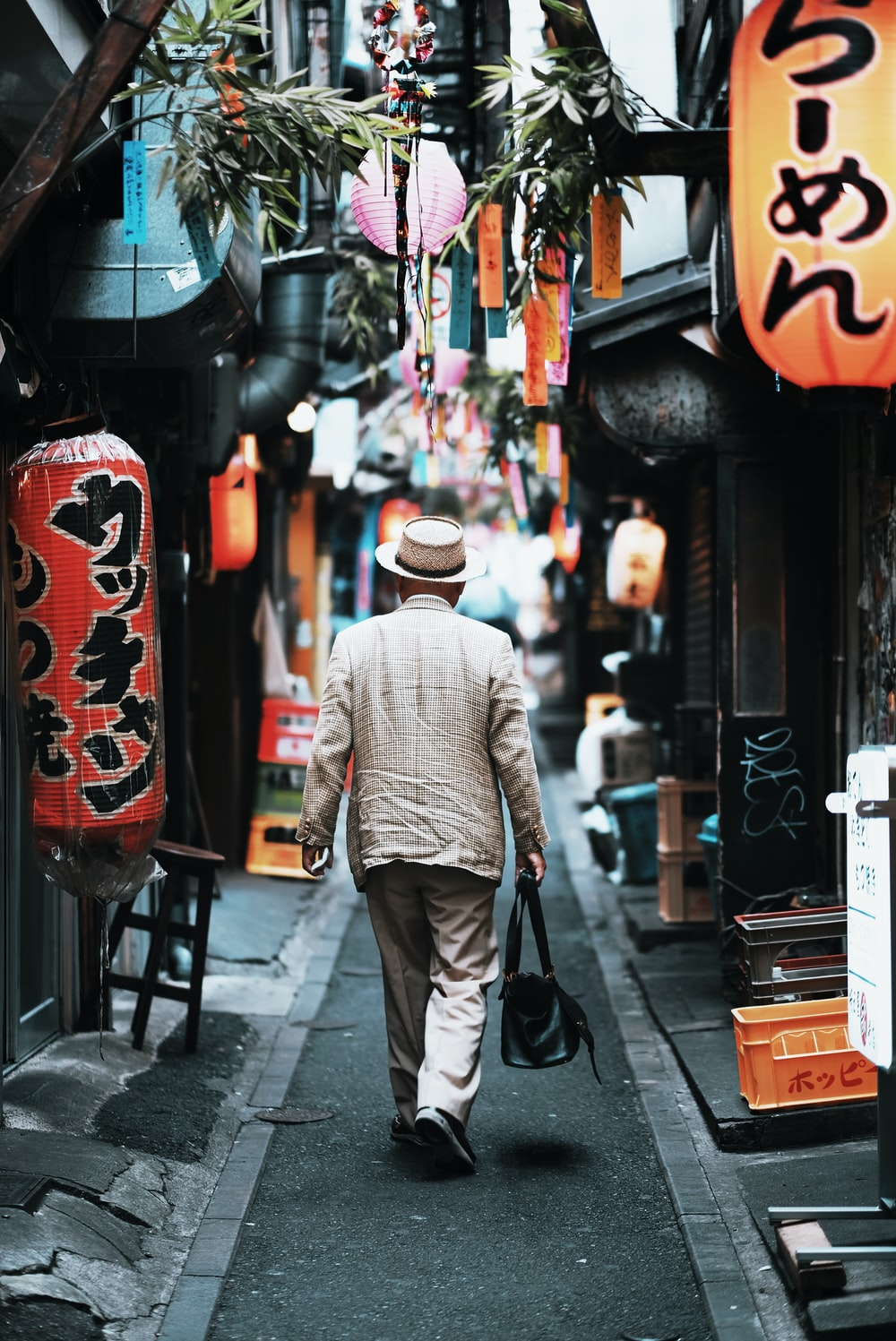 An elderly man in a suit in a narrow alley in Tokyo's Shinjuku district