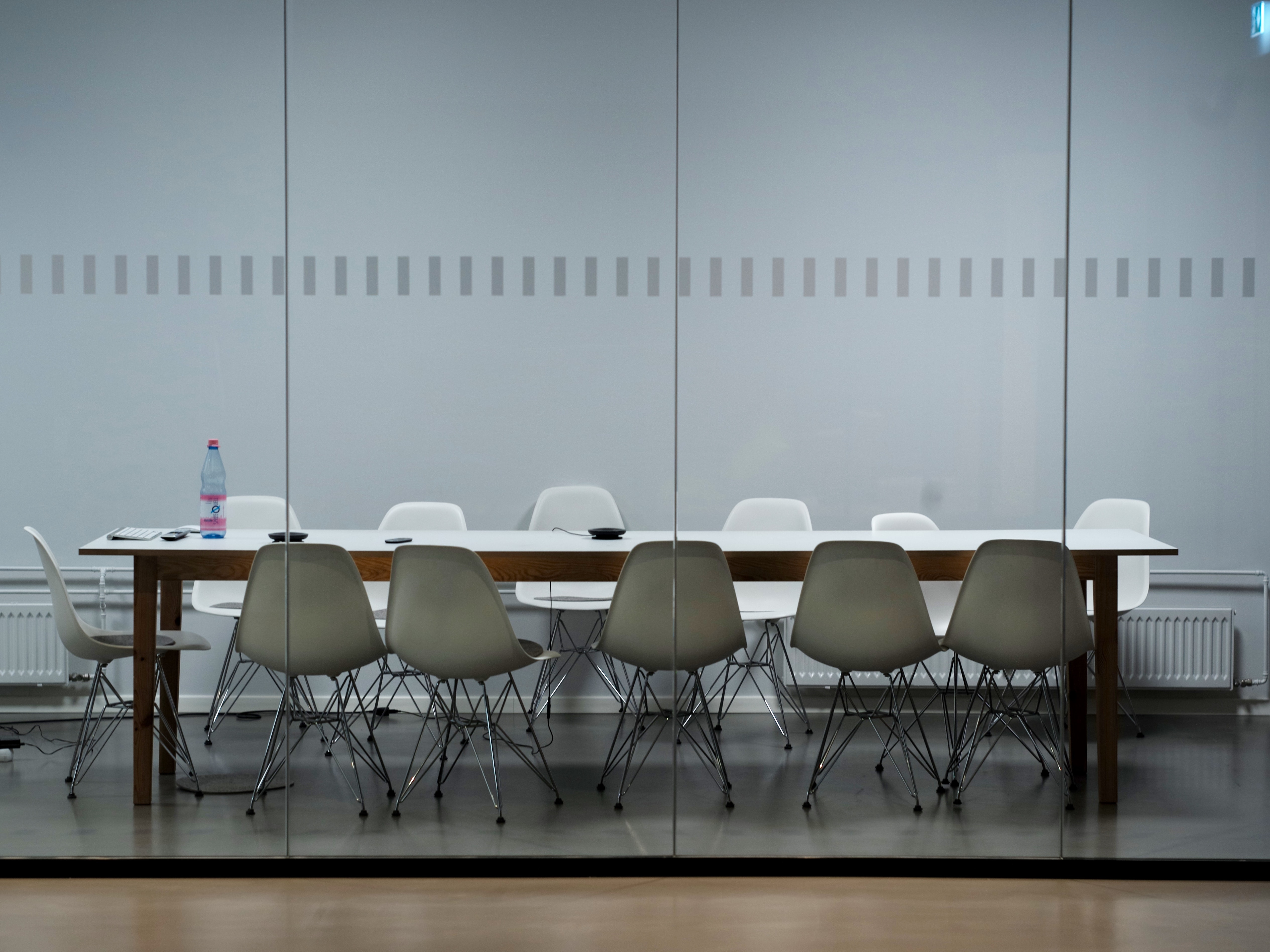 A table with white chairs in a meeting space in an office