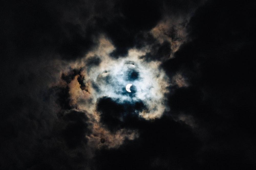crescent moon behind black clouds