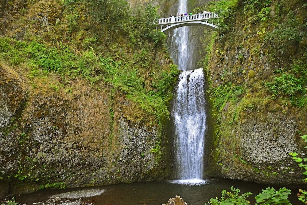 people standing on bridge above waterfalls during daytime