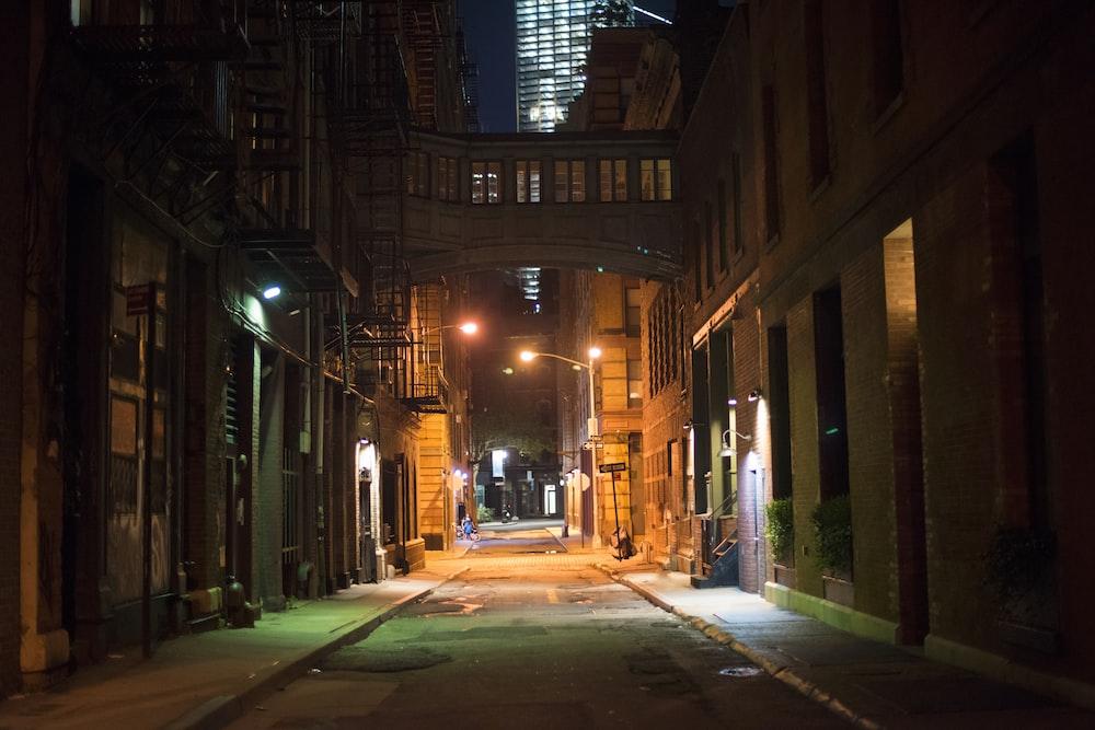 empty street in between of buildings during nighttime