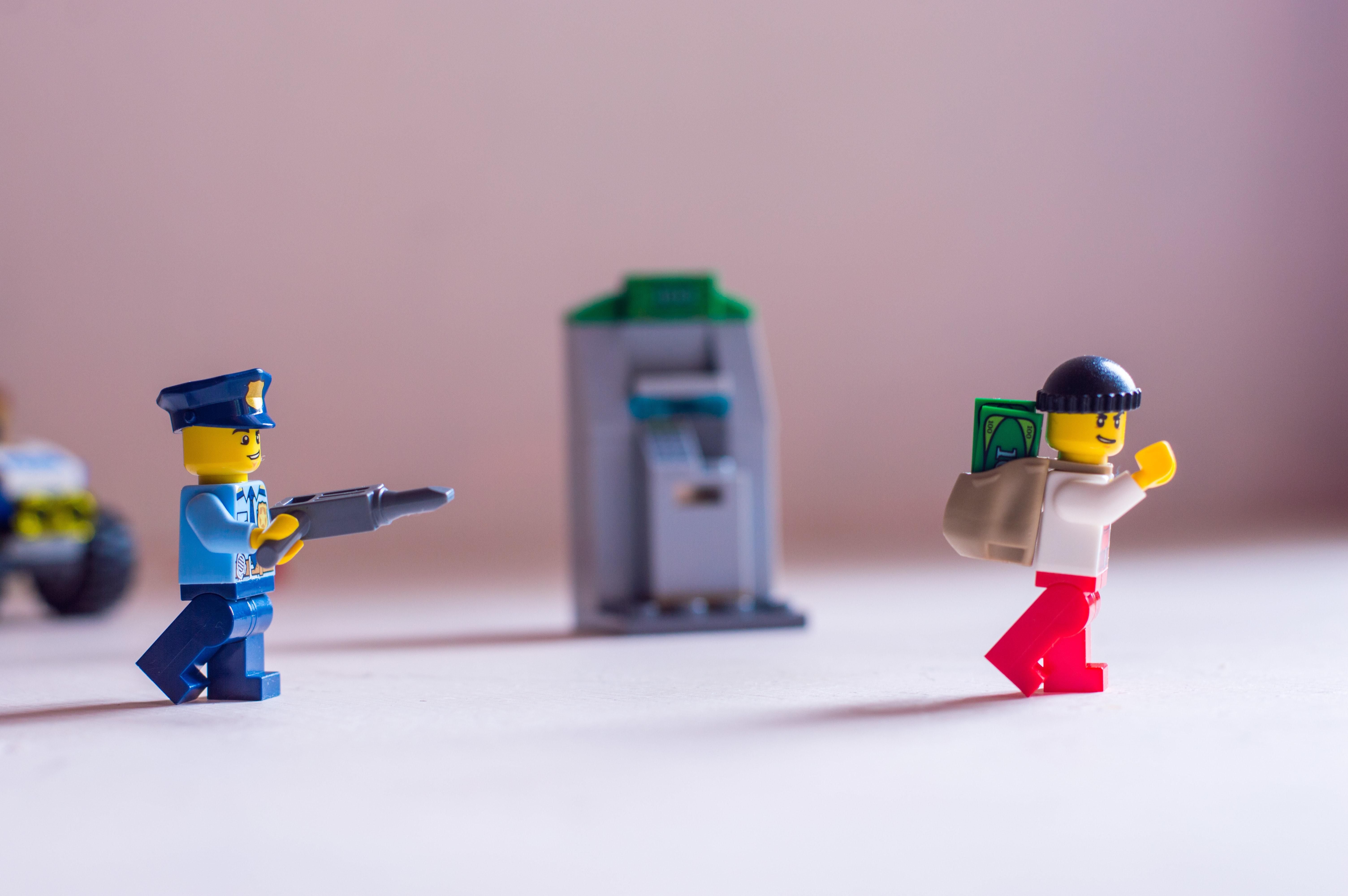 A Lego police officer pointing his gun at a robber.