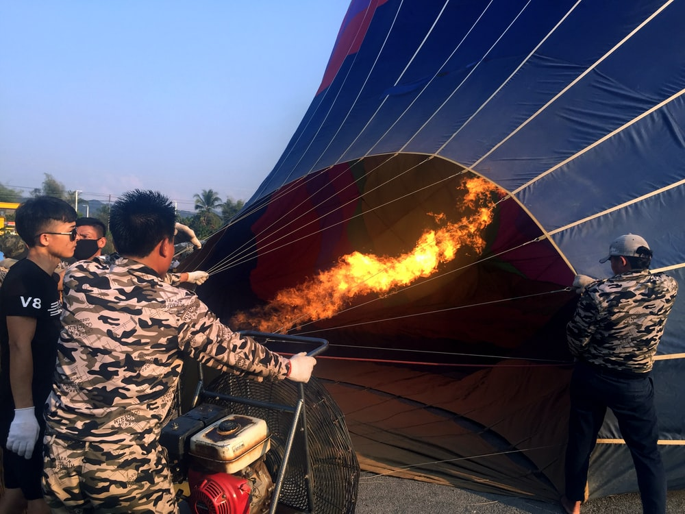 people blowing fire on hot air ballooon