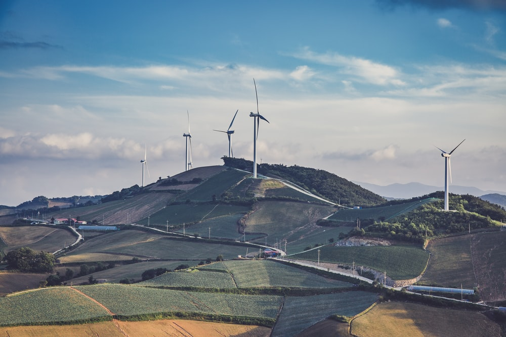 white windmills on top of mountain at daytime
