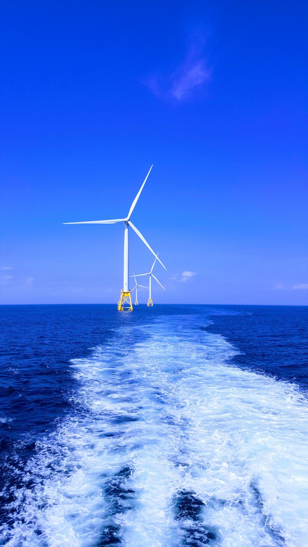 three white wind turbine on sea