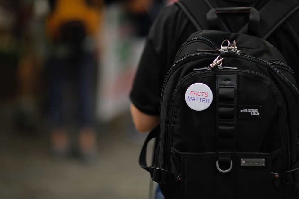 "A white""Facts matter"" pin on a black backpack on a person's back"