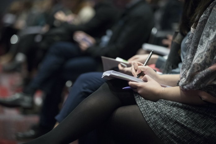 selective focus photography of people sitting on chairs while writing on notebooks