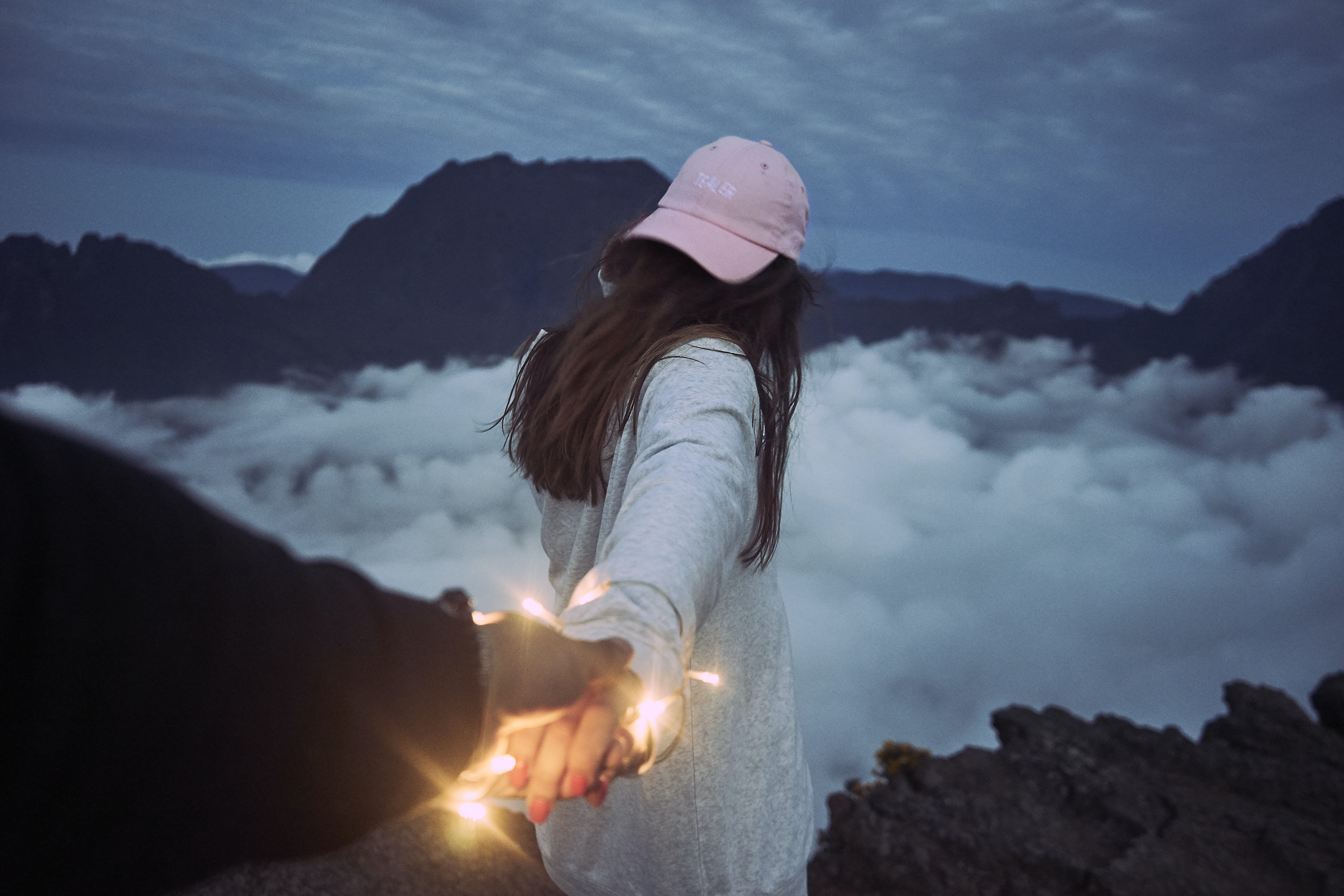 woman holding person's hand in front of clouds