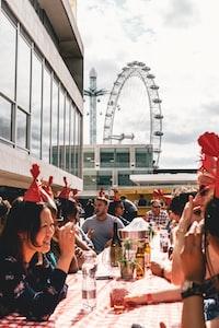 people dining outside building near ferris wheel