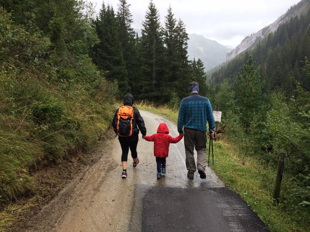 man, woman, and child walking together along dirt road