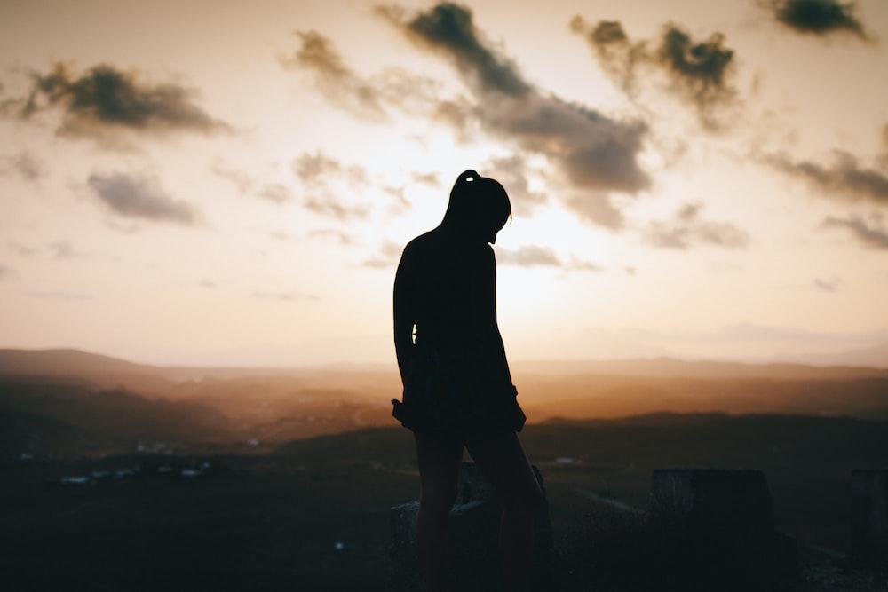 silhouette of woman standing near field
