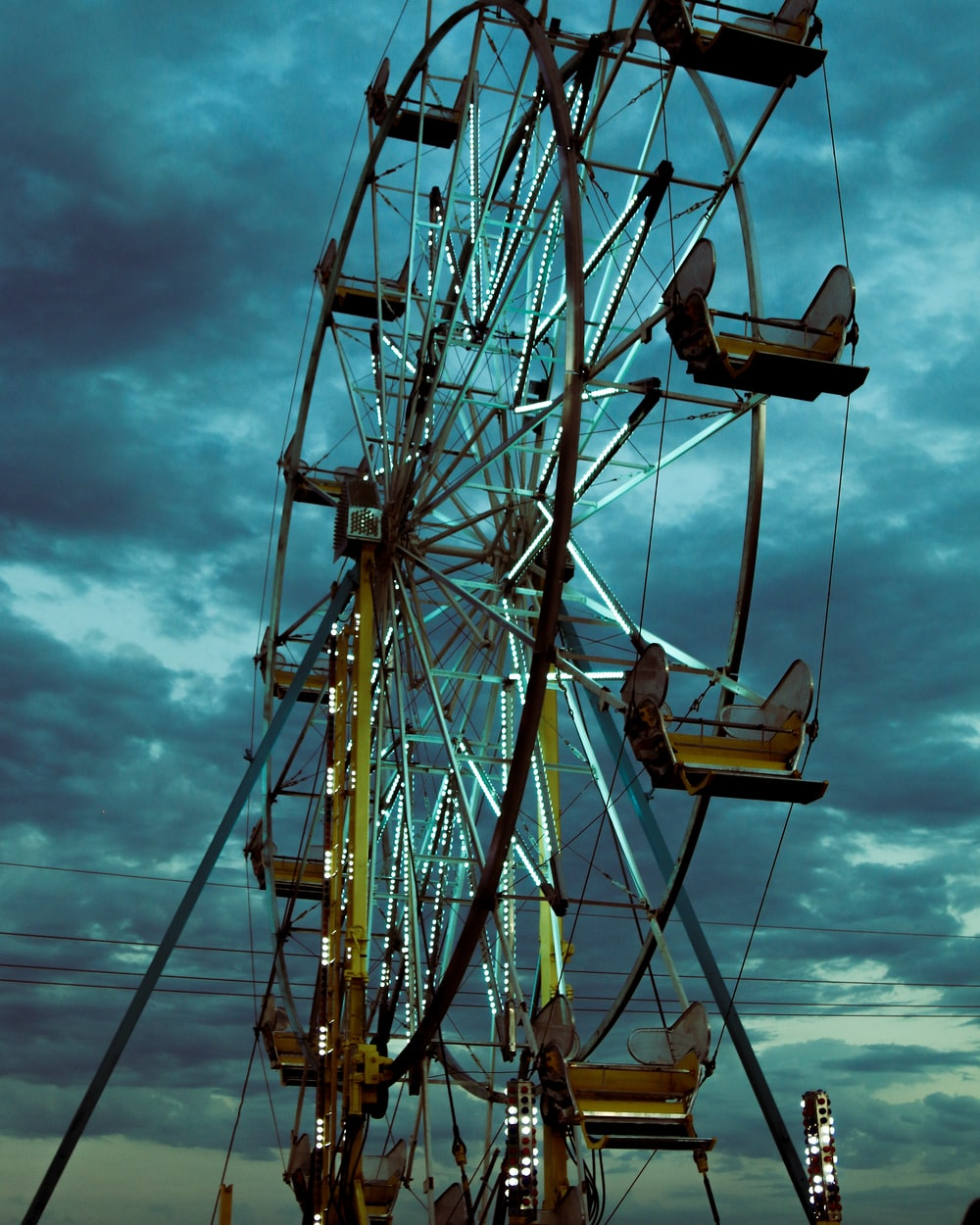 close up photography of ferris wheel under cloudy sky