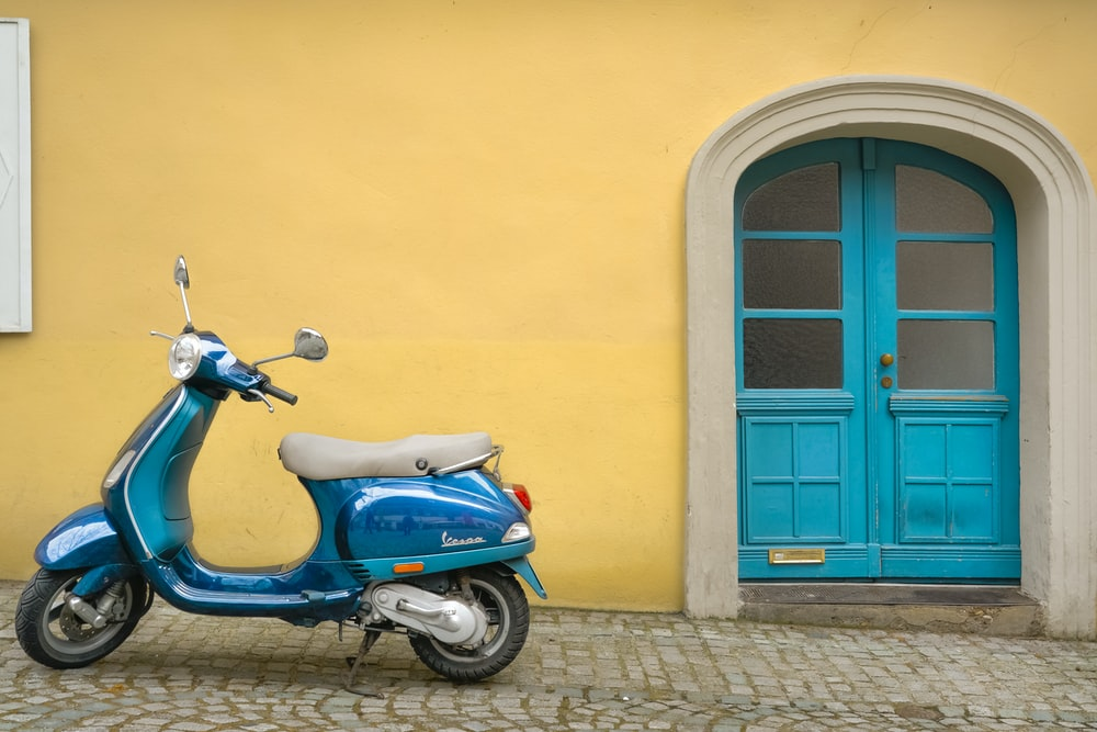 blue scooter motorcycle outside house