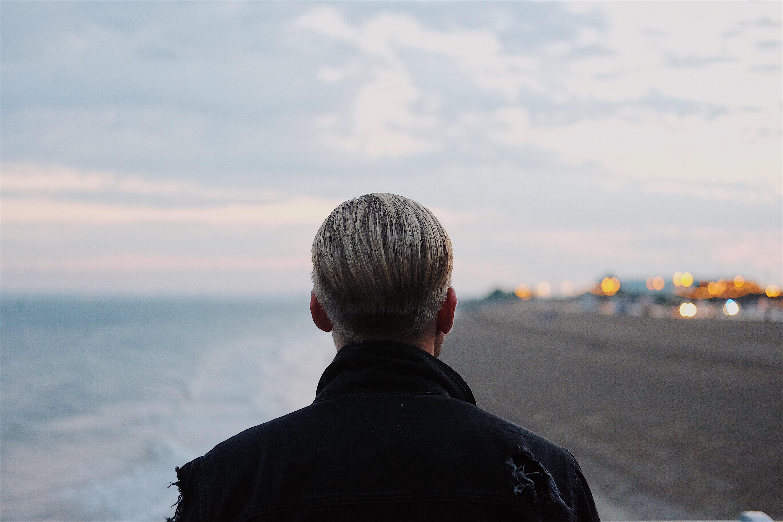 man in black coat walking on seashore