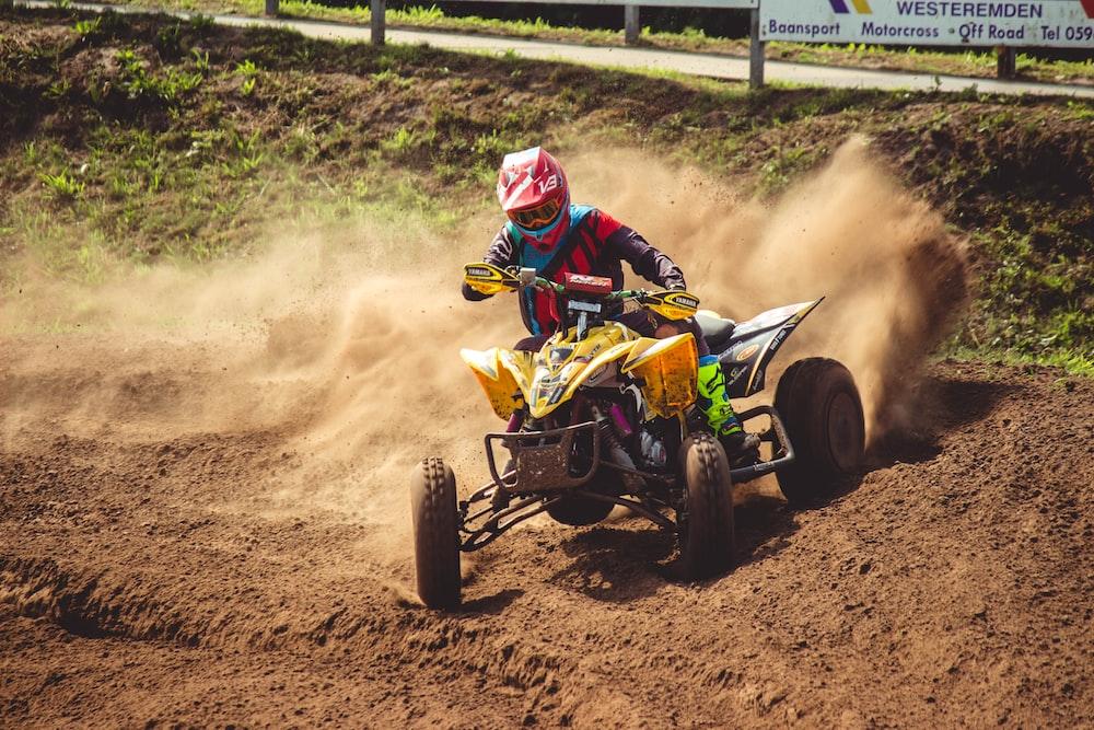man ridding yellow and black ATV