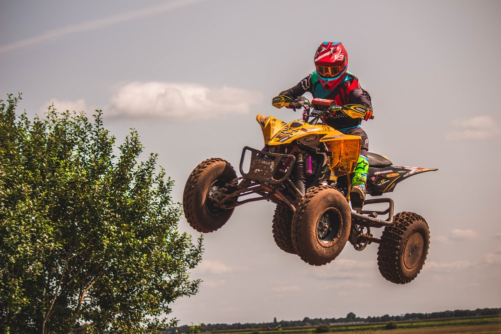 person riding yellow and black ATV