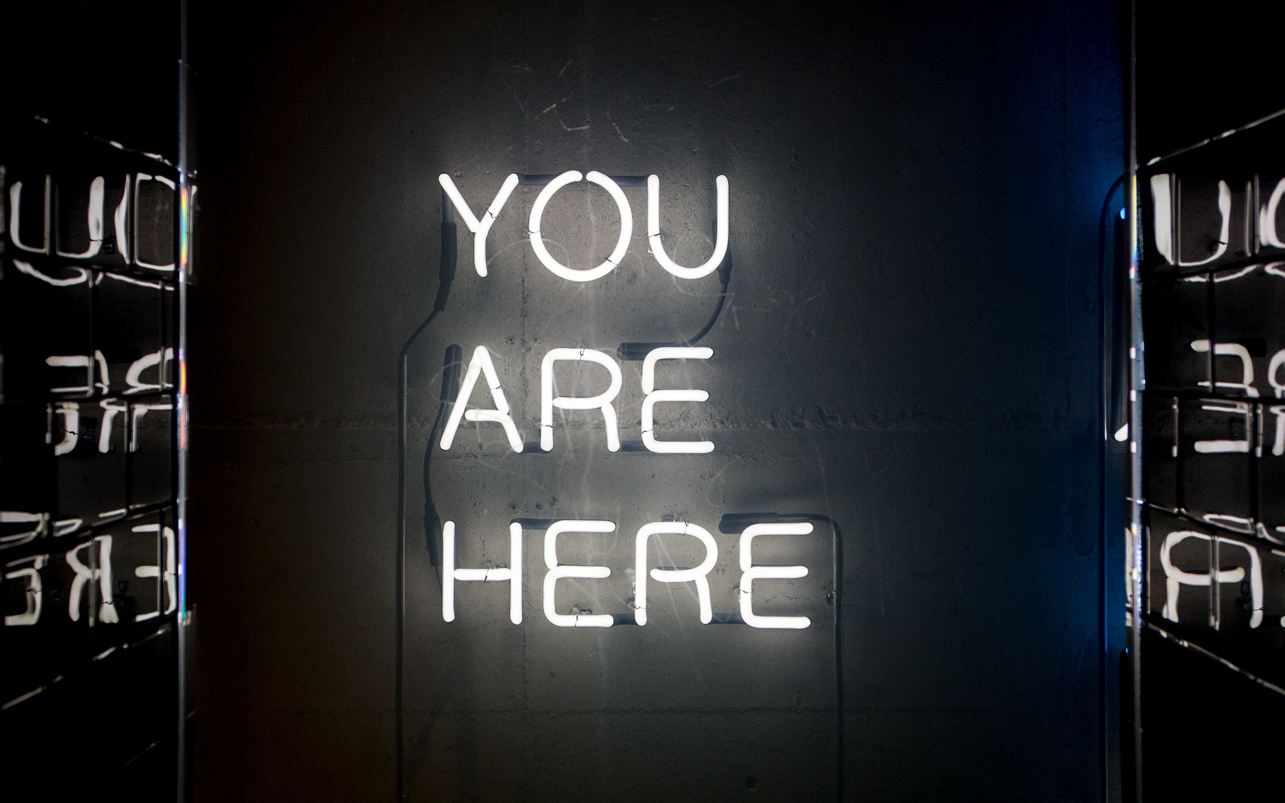 "A white neon reading ""you are here"" on a wall"