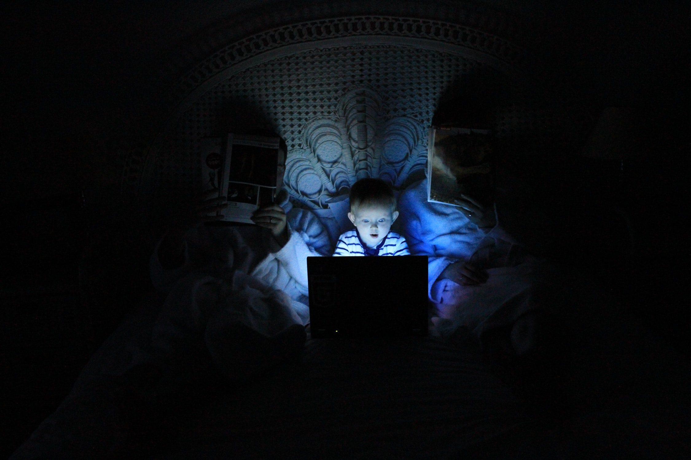 A child staring at a laptop screen with a captured expression at night while parents read a regular newspaper