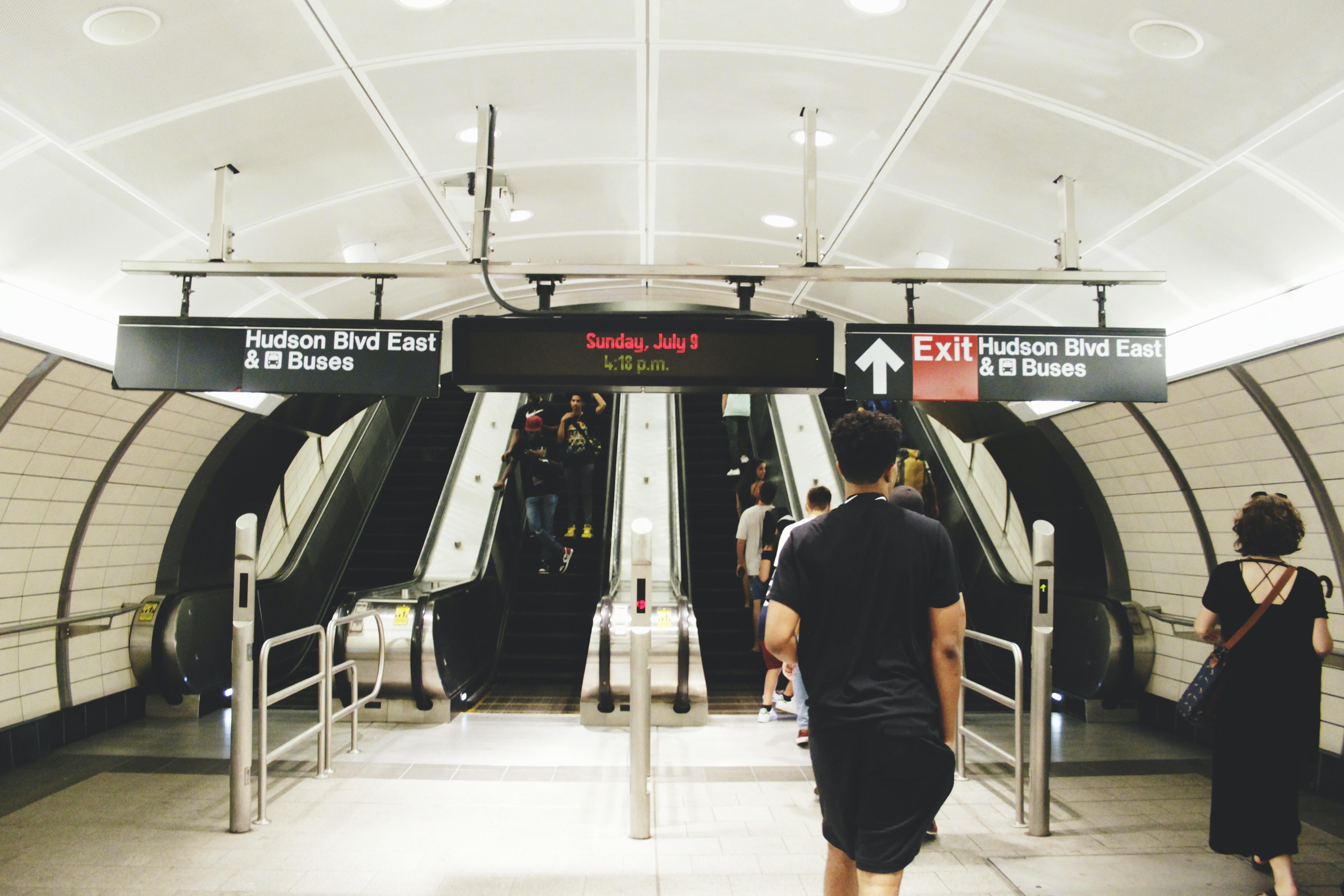 people walking towards escalator inside Bus station