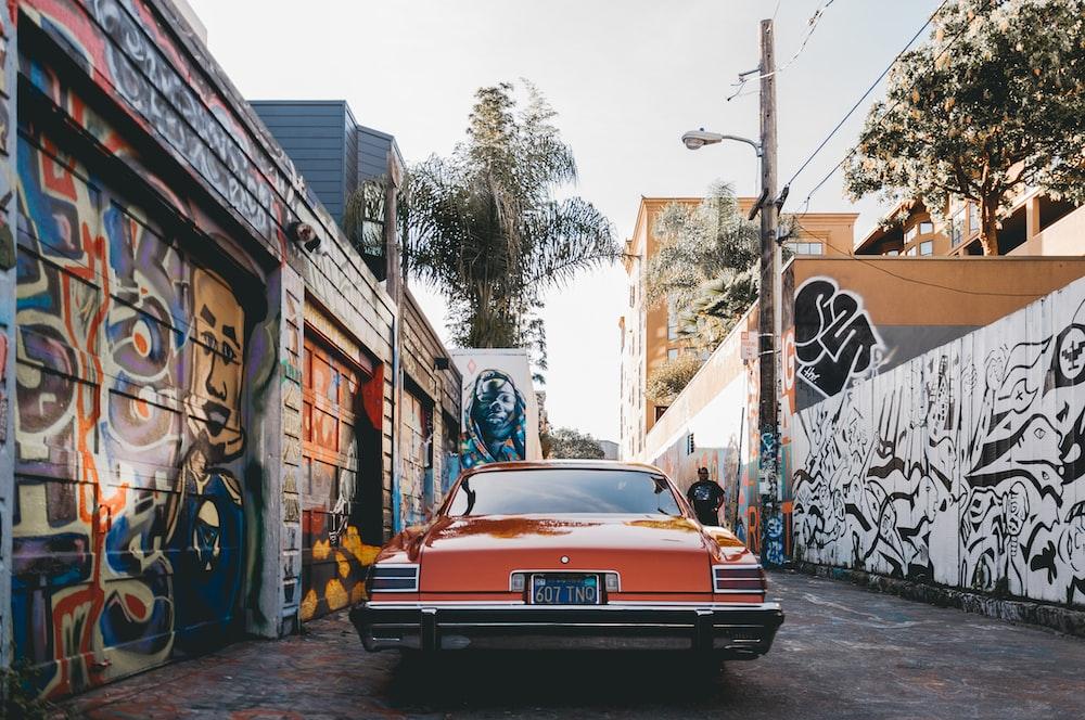 orange car parked between painted walls