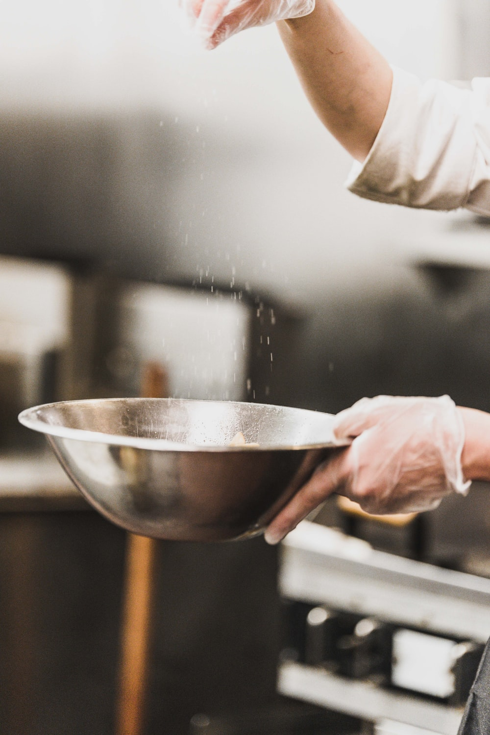 person garnishing on gray stainless steel bowl