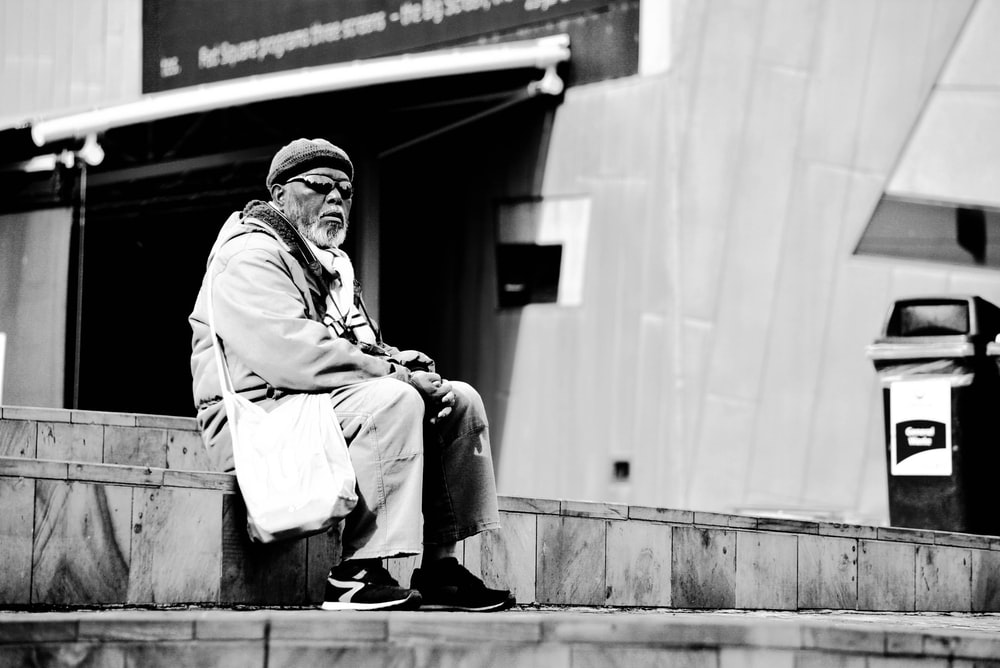 greyscale photograpy of man sitting on gray stair