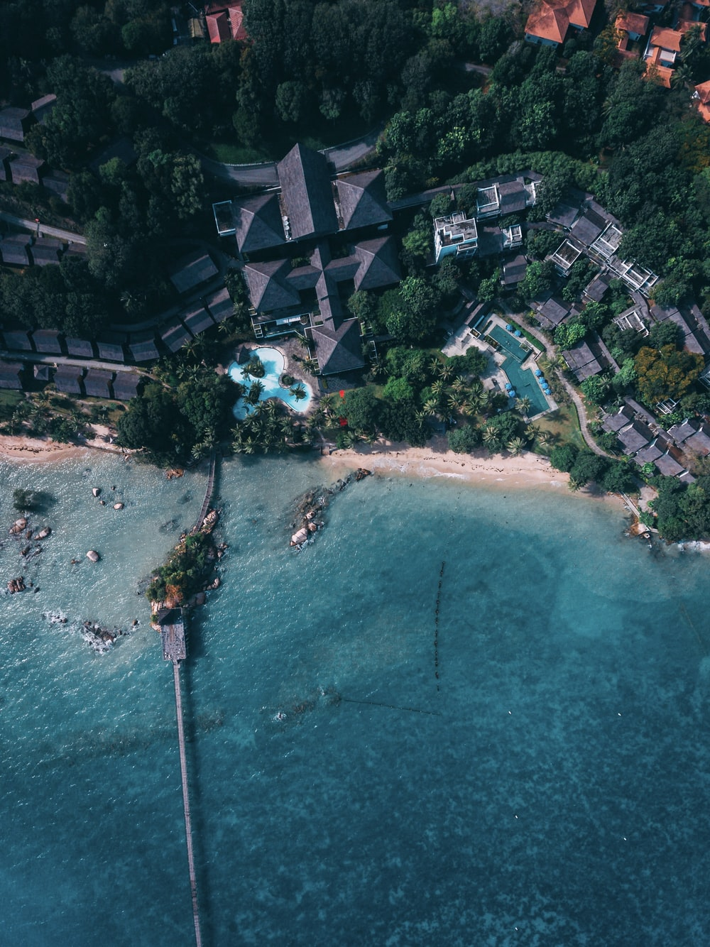 aerial photography of resort with pool by the beach