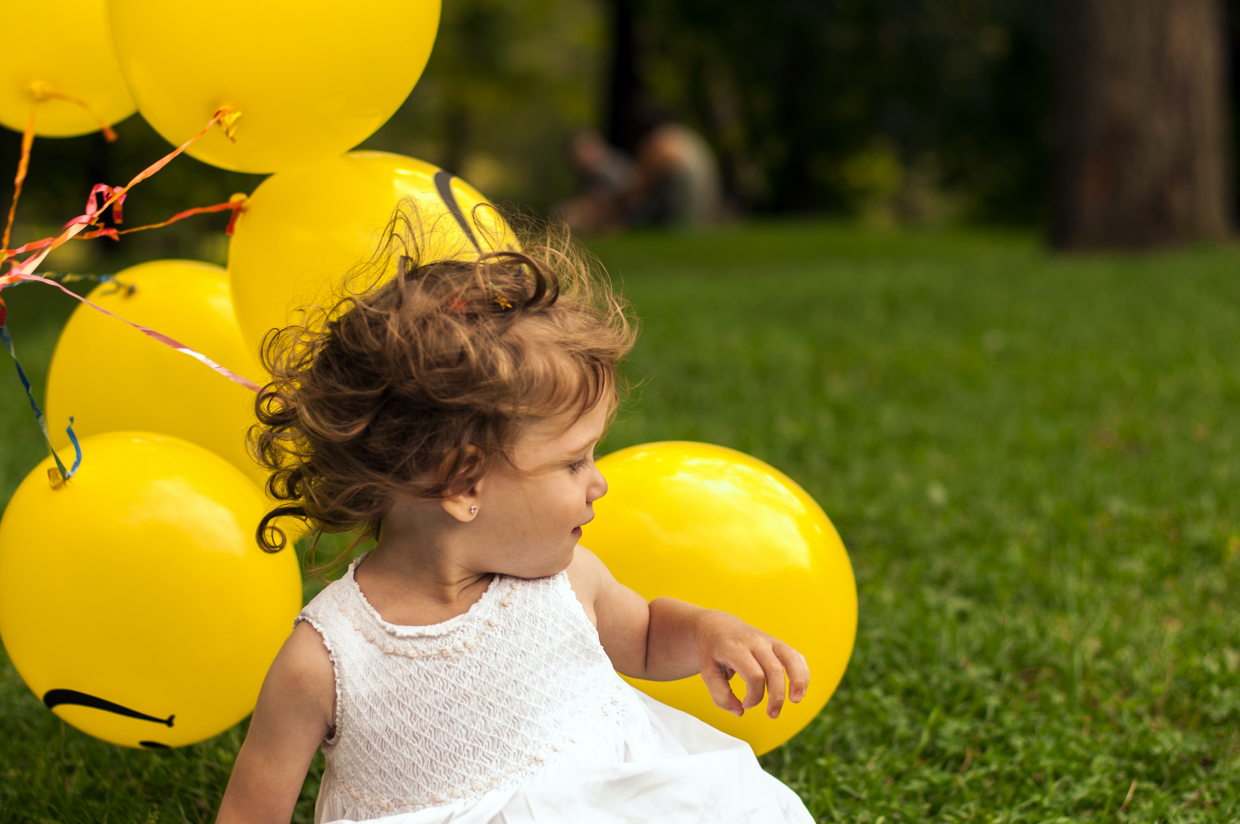 A little girl in a white dress sitting down next to a bunch of yellow balloons.