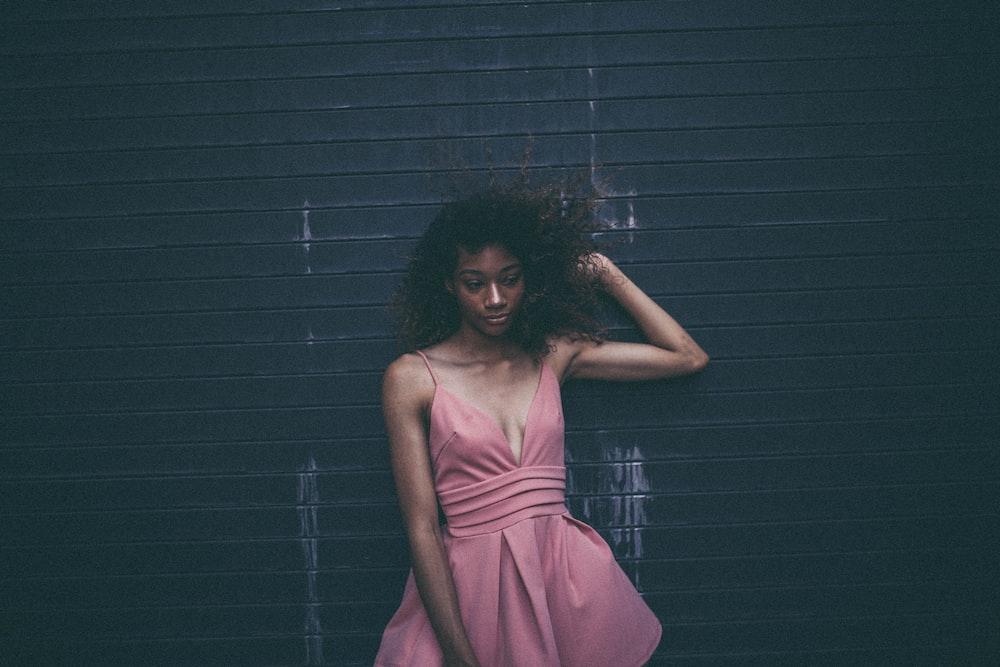 woman in dress leaning on black wall