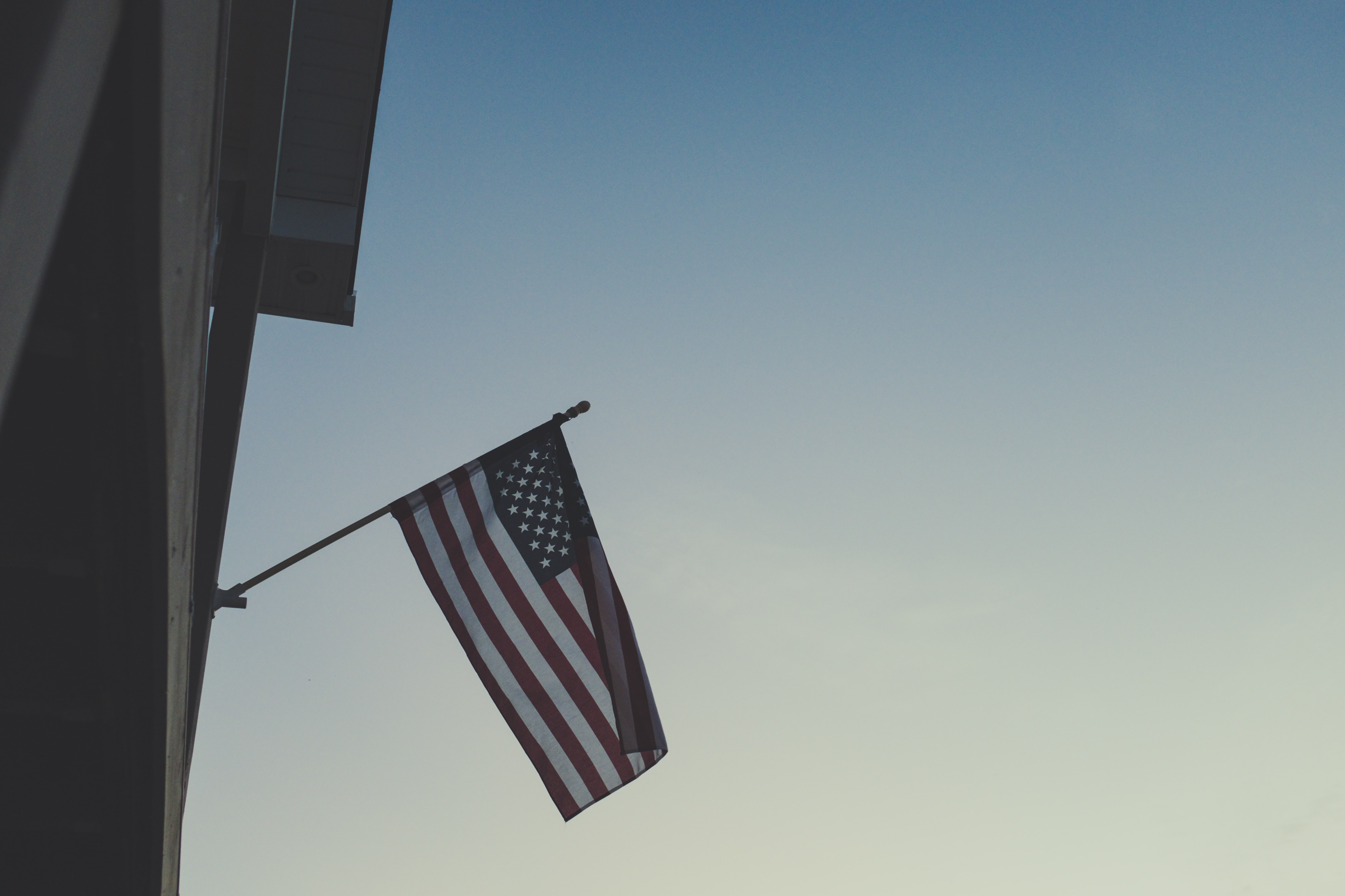 American flag flies off the side of a building in dim light