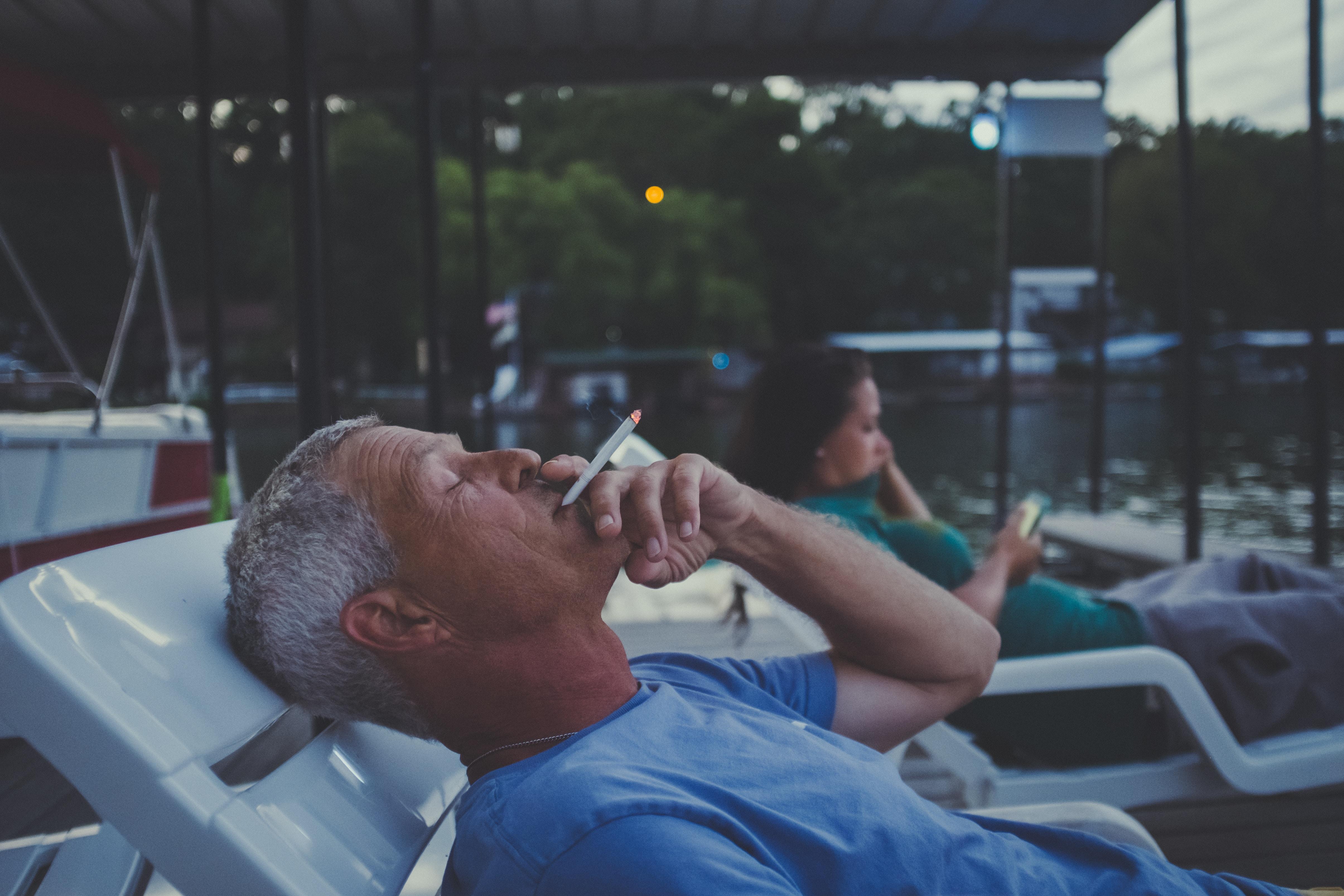 man lying on lounger while smoking cigarette