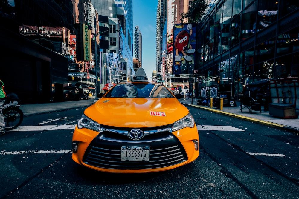orange Toyota car on road between buildings