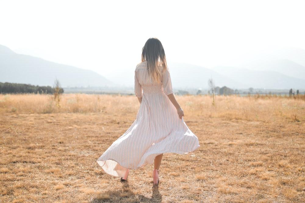 woman standing on plain brown field