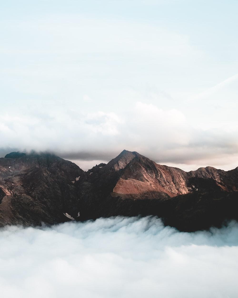 brown mountain under cumulus clouds