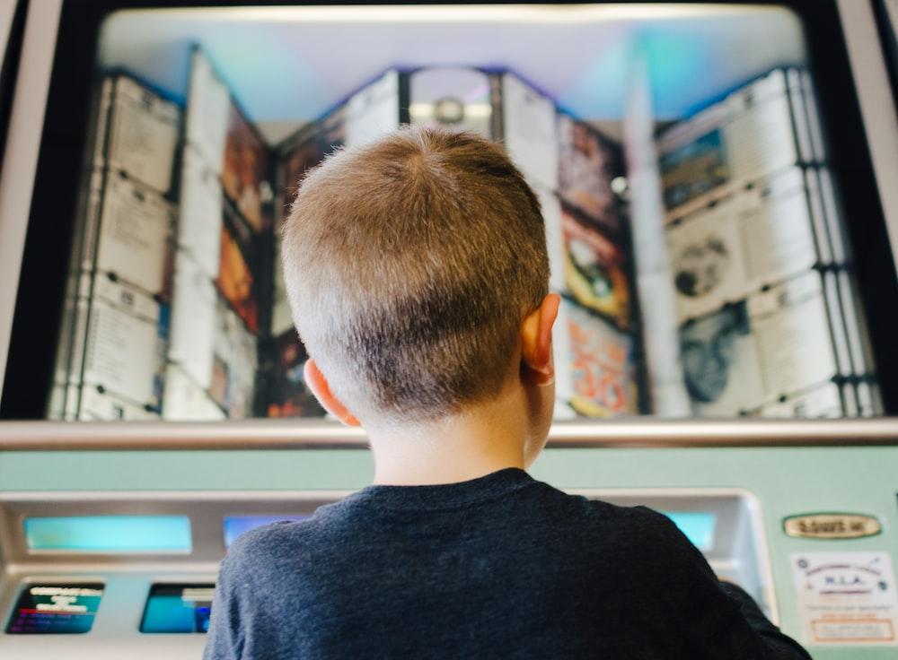 boy wearing black shirt on teal machine