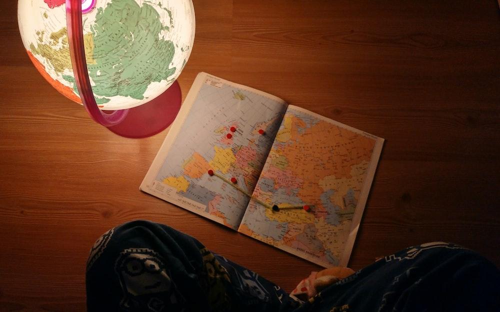 world map near desk globe on brown wooden panel