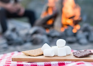 marshmallows and chocolate bar on brown wooden board