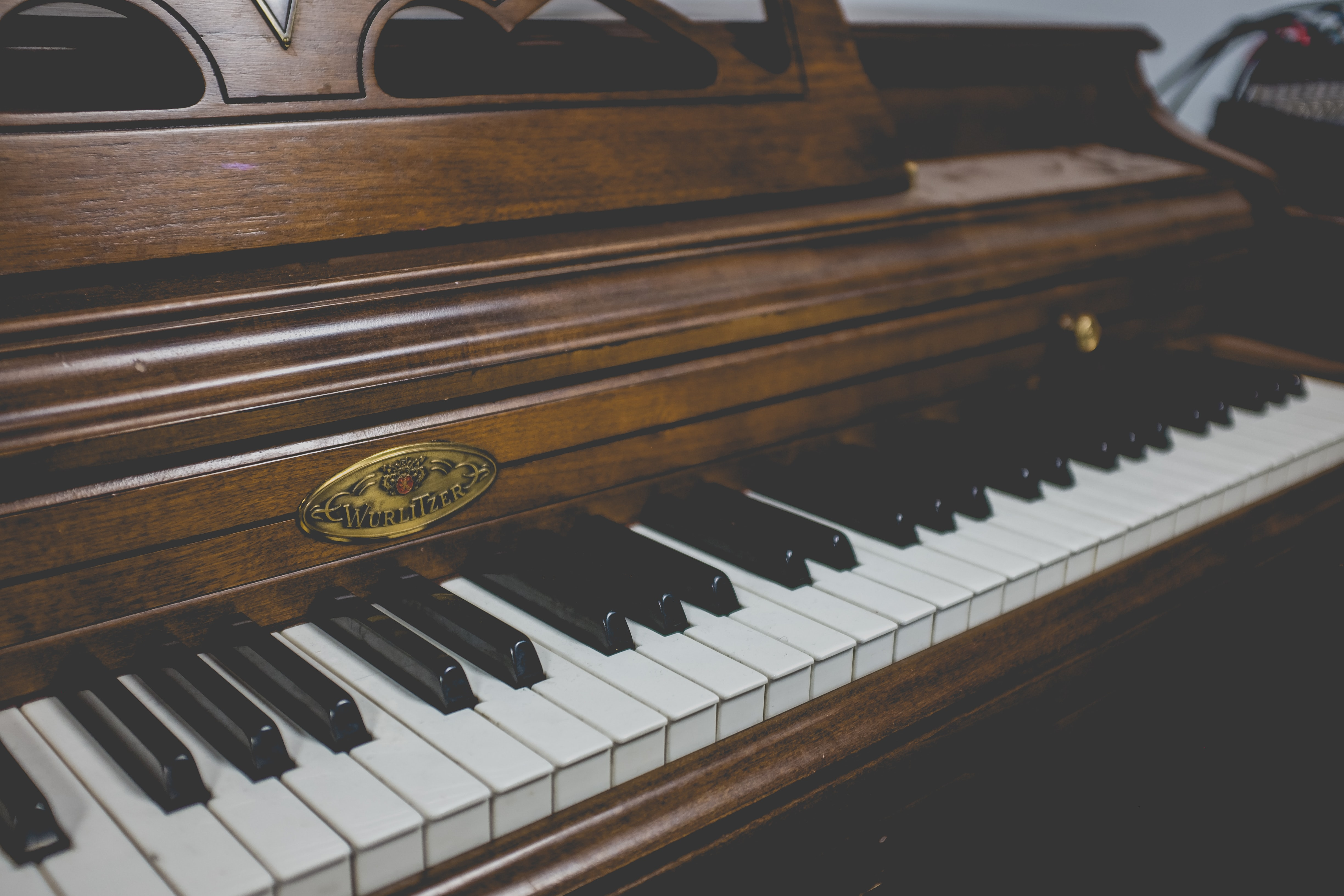 selective focus photography of brown and white upright piano