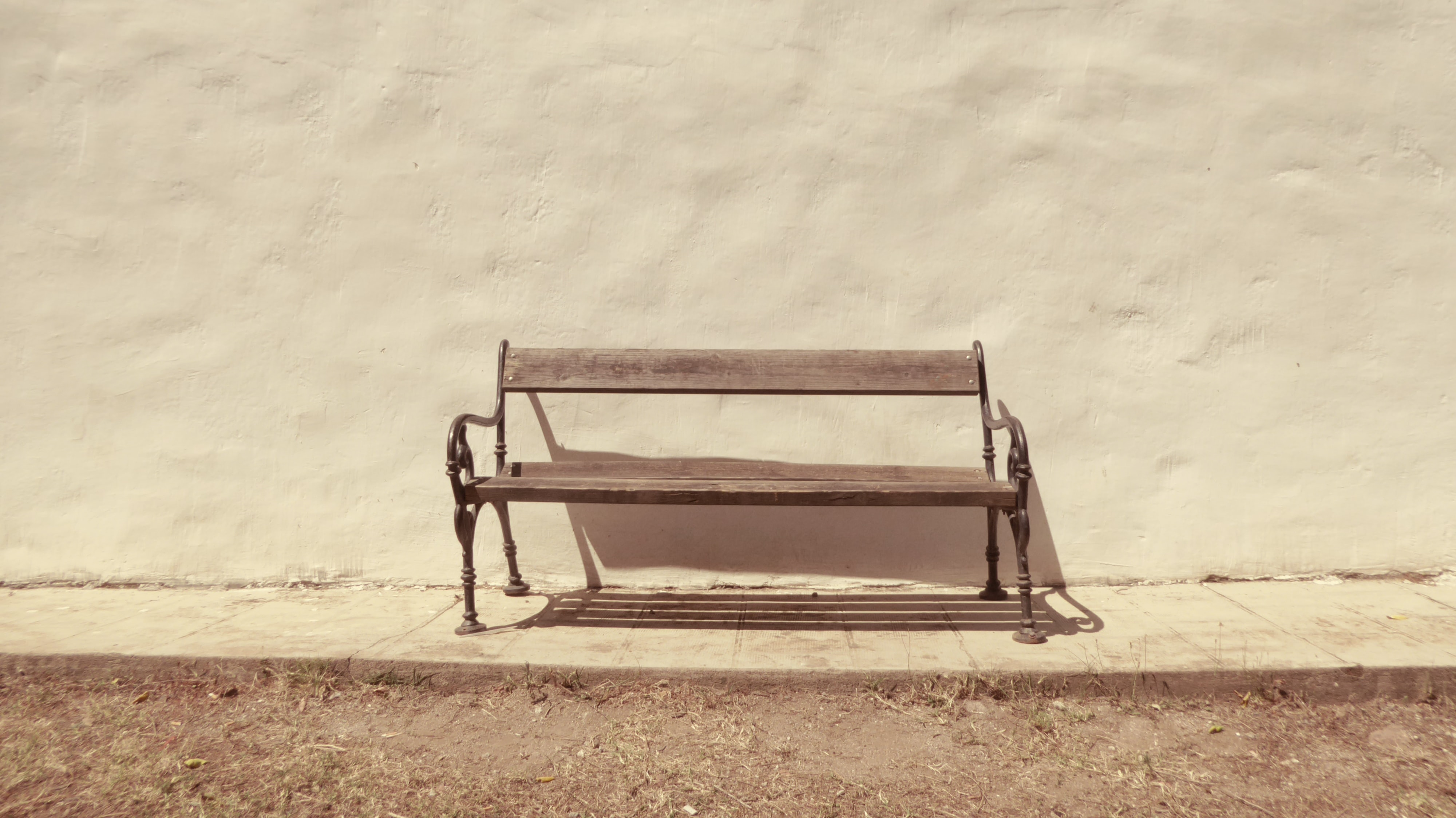 black bench in front of white wall