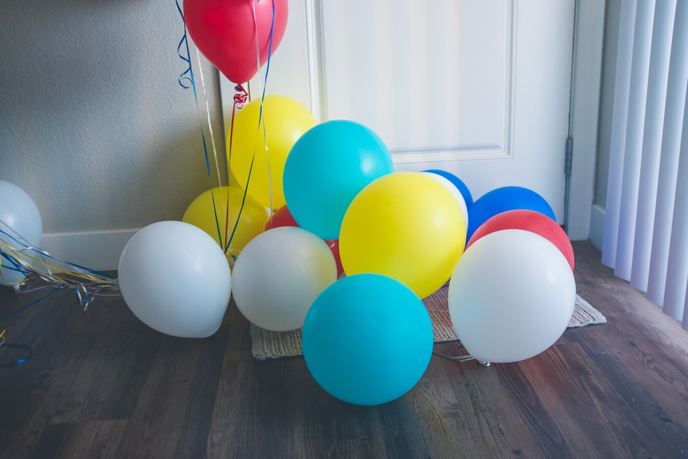 assorted-color balloons on floor near closed door