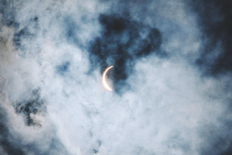 crescent moon under cumulus clouds