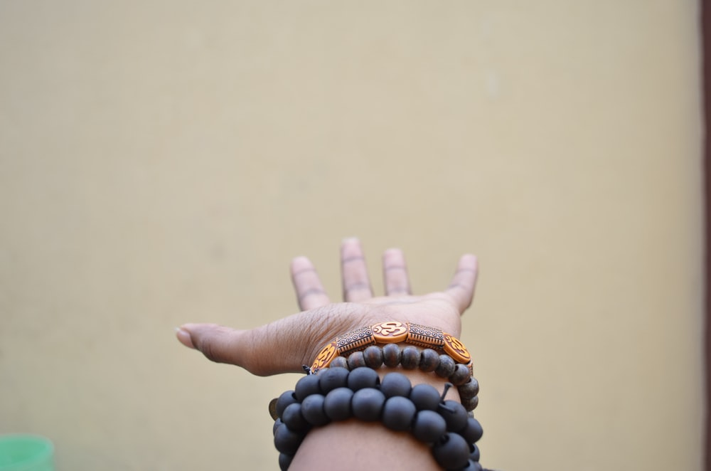 person hand with black beaded bracelets
