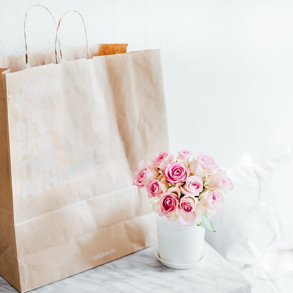pink rose bouquet beside brown paper bag