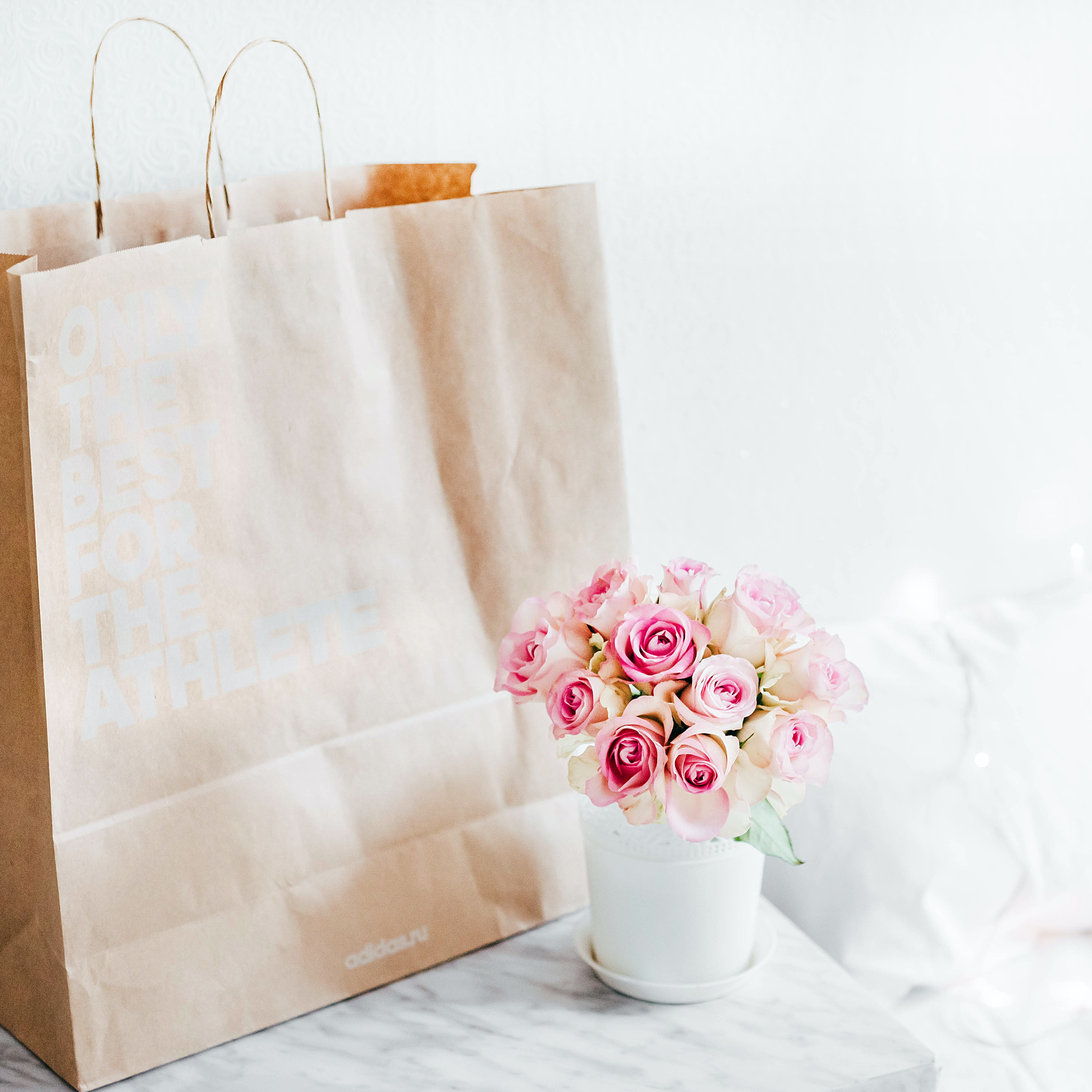 A cup of flowers next to a gift bag.