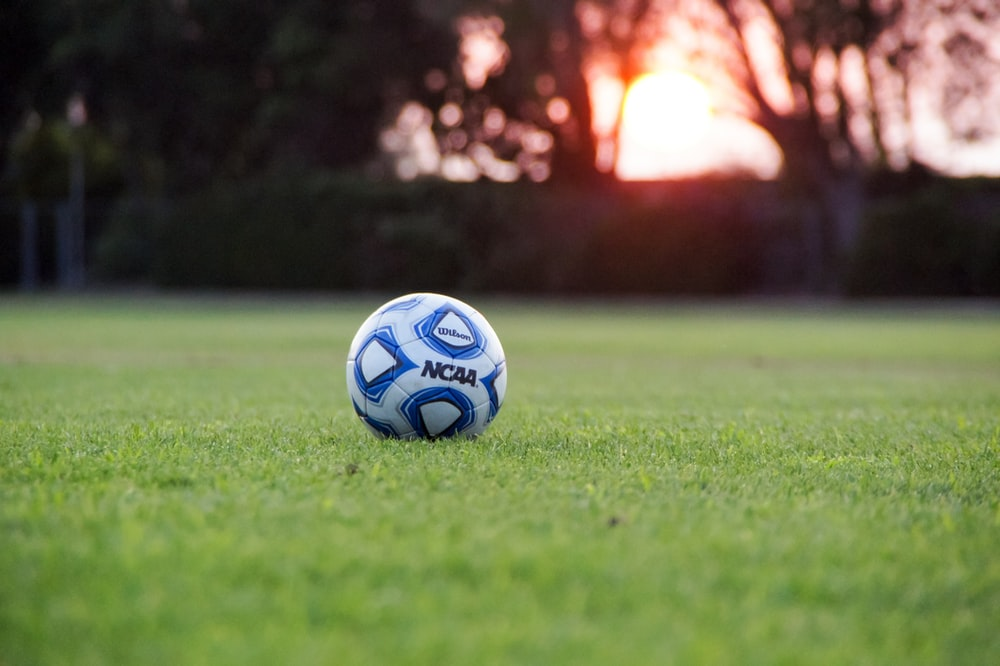 white and blue NCAA soccer ball on green grass field