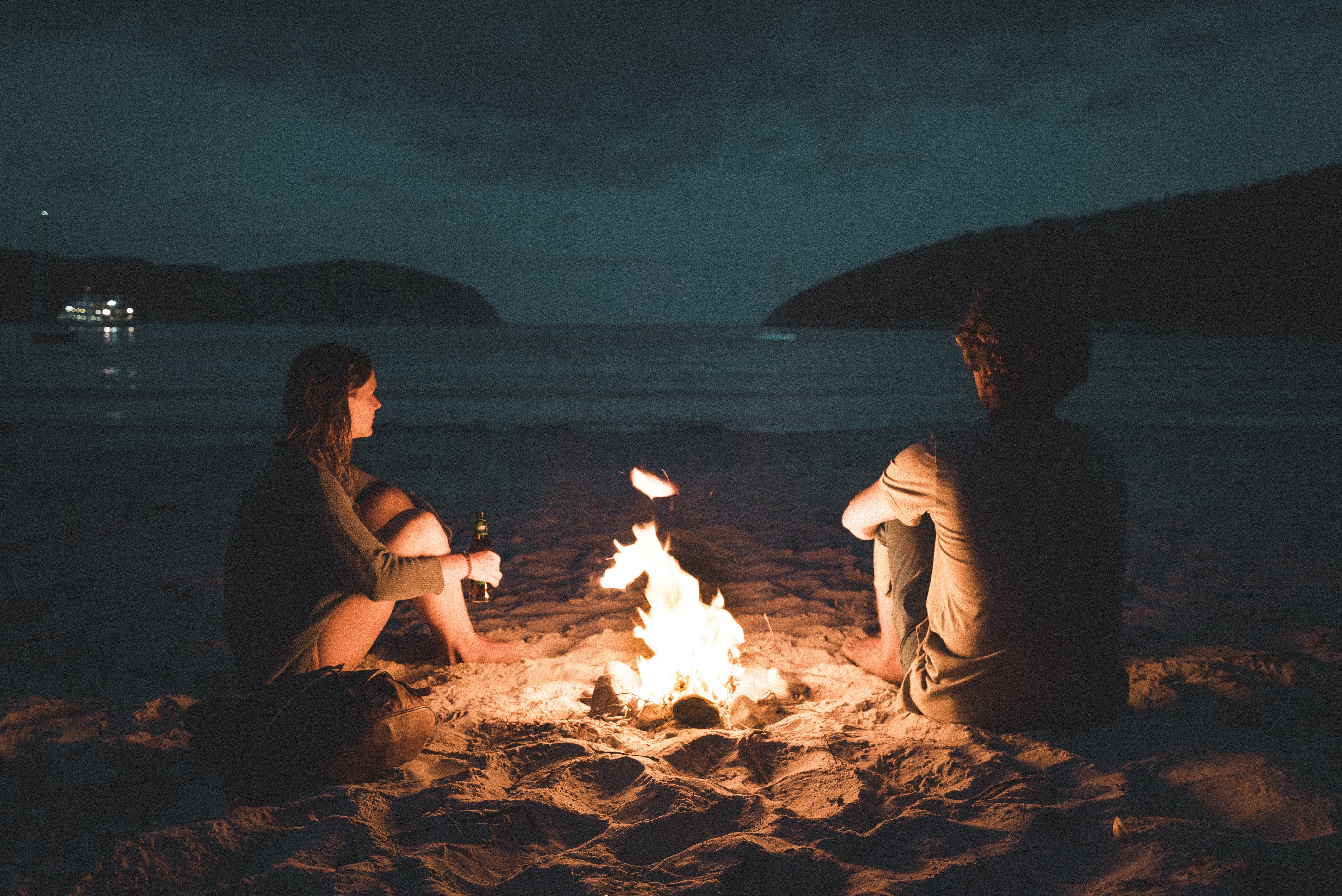 man and woman with bone fire sitting on seashore
